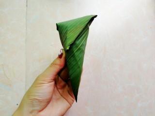杂豆蜜枣小米粽,再把顶端的往下折,如图,然后用粽绳绑起来
