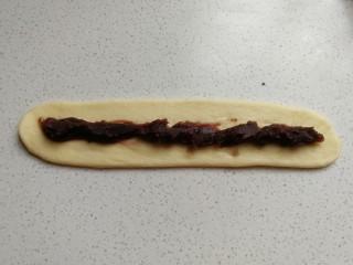 花环豆沙包,然后把长条状擀成扁平的长条片,再在长面片中间放上适量豆沙馅,把豆沙馅也整成长条型。