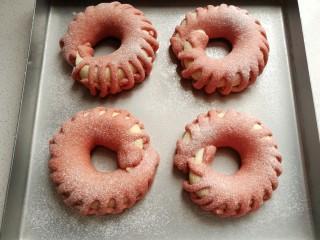 花环豆沙包,发酵好的花环包取出来再筛上一层高筋面粉,然后放入预热好的烤箱,中层上下火180度,烤约20-25分钟左右。(上次满意后要及时加盖锡纸,以免上色过深)