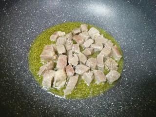 土豆烧牛肉,下入牛肉块煸炒至变色。