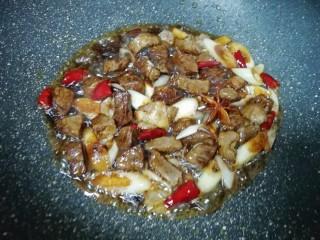 土豆烧牛肉,加入两勺红烧酱油和一勺料酒翻炒均匀。