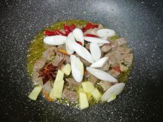 土豆烧牛肉,下入葱、姜、干红辣椒、八角和桂皮炒香。