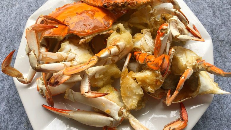 避风塘炒蟹,炸好捞出沥干油,放入盘里待用