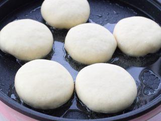 发面红糖饼,平底锅中倒入适量食用油烧热,将饼胚依次排放锅中