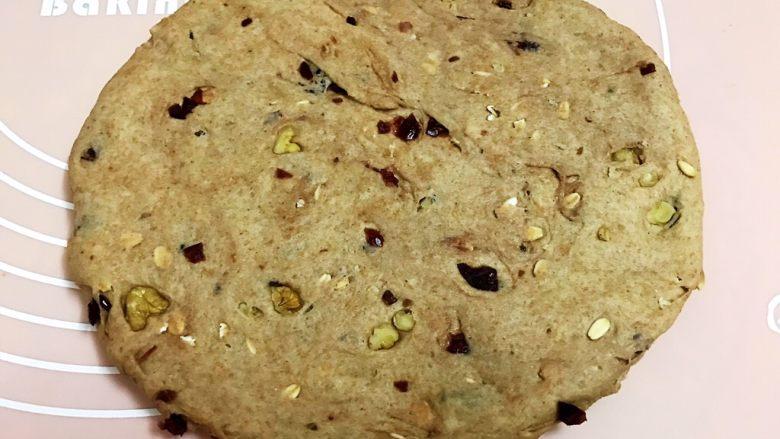 无糖低脂果干全麦面包,把面团取出排气,平分成2份,取一份擀成椭圆形