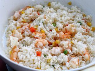 虾仁蛋炒饭,接着放入米饭炒散,然后不停的翻炒两分钟。米饭一定要用剩米饭,新蒸的米饭水分太大,吃起来发粘