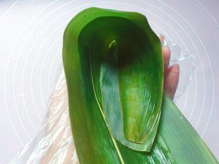 花生蜜枣粽,在粽叶的1/3处折起,折出一个漏斗形状(漏斗下方一定要紧密,不然会漏米);