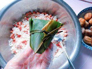 花生蜜枣粽,用绑粽绳在粽腰处扎紧打结,一个紧实漂亮的粽子就包好啦。