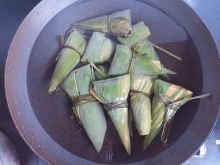 红豆红枣牛角粽,全部包好后放入煮锅,加入足量的清水(水一定要没过粽子),大火煮开转中小火煮一个小时,煮好以后在锅里再焖两个小时后捞出,口感更黏糯。