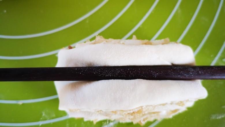 油渣花卷,用筷子按压(如图),筷子两边会上翘形成花形,然后用双手捏住两端向下折回即成花卷