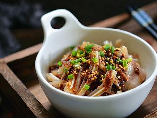 凉拌猪耳朵,放入碗中,将调料汁浇在耳片上,再撒点葱花点缀