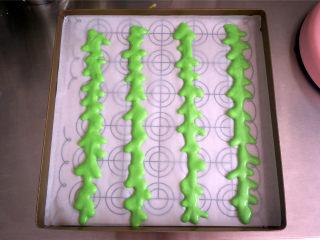 夏季私房热门的西瓜蛋糕,烤盘垫上硅油纸,裱花袋剪出一个小口,在烤盘上挤出几道西瓜纹路,放入烤箱中层,175度烘烤2分钟。这个烤盘是28*28cm的。