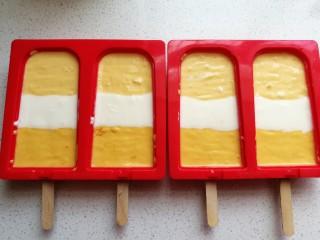 芒果酸奶雪糕,再轻轻震荡几下震平表面,可以借助牙签来回划动,用牙签划动即能平整表面又能划出里面的气泡空洞。