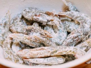椒盐虾,虾洗净,用纸巾轻轻拍干。用玉米淀粉把它们全身裹起来。