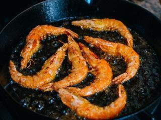 椒盐虾,把油加热。迅速将虾放入油中,每只虾之间留有一定的空隙,将虾分批油炸,每边煎30秒。