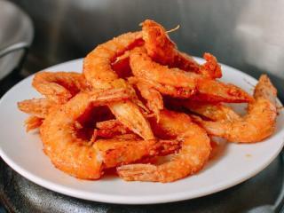 椒盐虾,虾捞起来放盘子里,撒上盐和胡椒粉来调味。