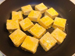 红烧豆腐(锅塌豆腐),锅里放油,大火烧热后迅速放入裹了蛋液的豆腐块,转中小火。