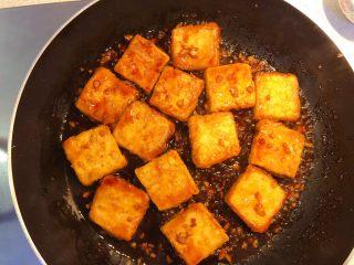 红烧豆腐(锅塌豆腐),加入煎好的豆腐块,把汤汁烧开,再将豆腐翻面,全部裹匀。