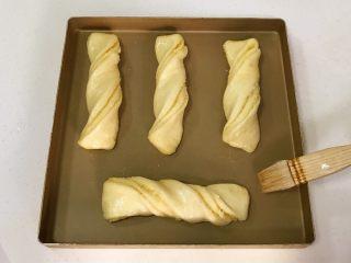 椰蓉奶香面包棒,放入烤箱中进行二发, 烤箱底层放一碗温水保持湿度,二次发酵温度38度左右,湿度为85%,发至2倍大取出,给面包表面刷上鸡蛋液。