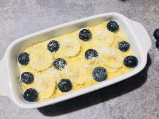 香蕉蓝莓烤燕麦,把剩下的香蕉片和蓝莓摆在上面,撒上椰蓉。