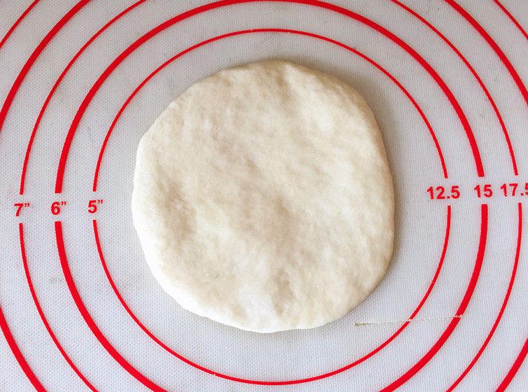 日式红豆包,取一份松弛好的面团压扁,用擀面杖擀成圆形面皮。