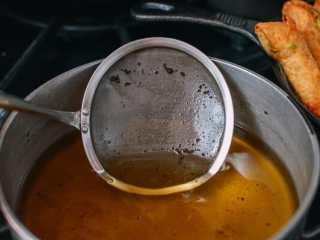 牛油果蛋卷,在煎炸过程中,要用细滤网来去除油里面的颗粒。
