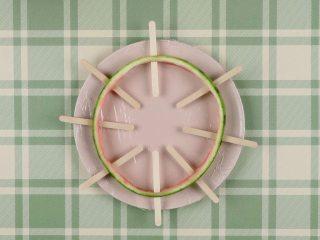 免模具西瓜雪糕,将瓜皮置于保鲜膜上,插入冰棒棍