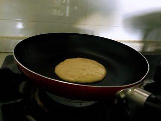香蕉松饼的健康做法,调小火,不用放油,舀入一大勺面糊,待面糊表面起泡,即可翻面。