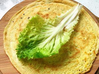 快手营养早餐09,没有黑芝麻的这一面朝上,放一片生菜叶;