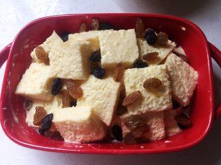 焗烤英式布丁,表面撒上葡萄干,如果有剩余的蛋奶液,可以沿着碗壁轻轻倒入