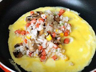 快手营养早餐13,在表面蛋液没有完全凝固时,放入适量炒饭,静待蛋液完全凝固,轻轻晃动平底锅,蛋皮可以在锅底滑动时,准备出锅;