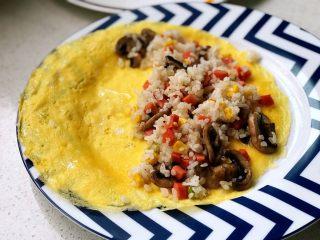 快手营养早餐13,将蛋皮和炒饭一起,缓缓从平底锅滑倒至餐盘,要小心+耐心,不可心急,免得破坏蛋皮完整性;