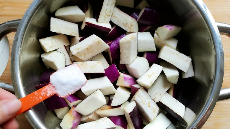 番茄烧茄子,在茄子中加入两勺食盐,拌匀后腌制半个小时。