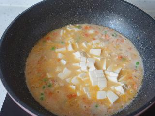 咸蛋虾仁豆腐煲,水开后倒入豆腐,小火煮三四分钟
