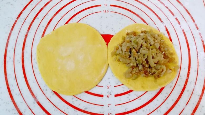 南瓜油渣包,取一个小剂子揉光滚圆,擀成包子皮,放上油渣馅。
