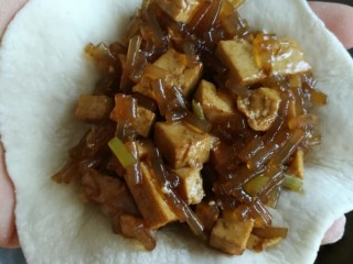 豆腐粉条蒸包,取一个面皮,倒入适量调好的馅