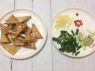 超级下饭的香煎豆腐块,豆腐两面煎金黄后夹出来备用。  小米椒切粒;大蒜剁成蓉;香葱切小(葱梗和葱叶分开)。