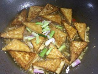 超级下饭的香煎豆腐块,等水少一半左右时,放入葱梗,同时给豆腐块翻面。