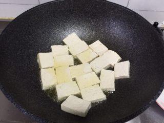 金针菇炖豆腐,锅里放油烧热,加入豆腐块