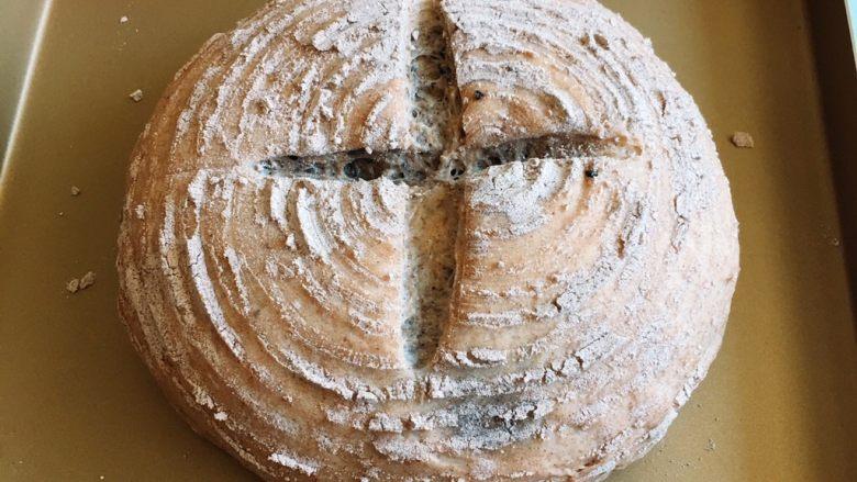 芝麻核桃黑麦包,发酵完成后倒扣在金盘中,用锋利的刀划十字。