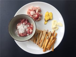 豇豆香干炒肉丝,将肥肉和瘦肉分开分别切丝,瘦肉加入适量淀粉拌匀;大蒜生姜切片;豆腐干切条。