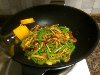 豇豆香干炒肉丝,倒入适量生抽翻炒10秒。