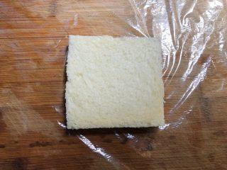 自制三明治,菜板上铺一张保鲜膜,放上一片吐司