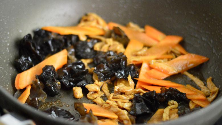 胡萝卜木耳炒肉丝,加入胡萝卜和木耳一起拌炒,炒至断生