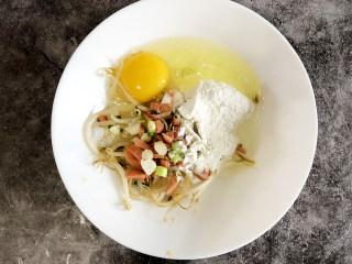 营养早餐豆芽饼,打入一枚鸡蛋到进行搅拌,搅拌均匀再倒入适量的面粉,直至粘稠