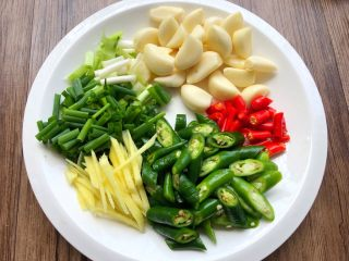 红烧鳝段,蒜头洗净去皮,小米辣切段,青辣椒切段,姜去皮切姜丝,葱切葱段