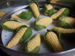 象形玉米,每两片叶子包住玉米底部,底部捏合在一起,搓出小尖。待锅里的水烧开后,放上蒸笼,隔水蒸10-12分钟