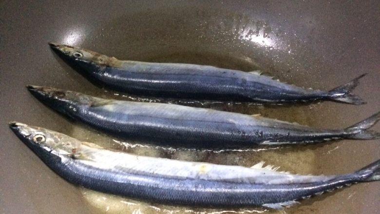 香煎秋刀鱼,6、放入秋刀鱼,小火慢煎。  让它们安静地待着,不要去动。  小贴士:注意看照片中,鱼旁边的一些花白的盐,这就是热油不能将盐全化开的状态。虽然看着盐多,其实热油的含盐量处于饱和状态,此时鱼主要通过油来吸收盐的味道,每次靠着这点就必定煎出咸淡适宜的香煎鱼。