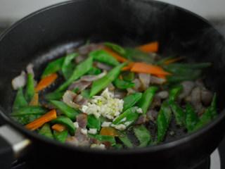 培根炒荷兰豆,放入蒜蓉,翻炒均匀