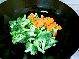 西兰花炒胡萝卜,下入西兰花和胡萝卜翻炒至变色。